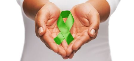 healthcare and medicine concept - female hands holding green organ transplant awareness ribbon