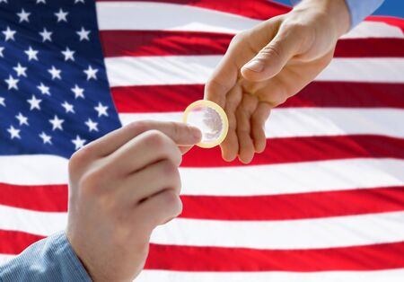 educacion sexual: personas, homosexualidad, sexo seguro, la educación sexual y el concepto de la caridad - Primer plano de pareja de sexo masculino manos de los homosexuales que dan condón sobre fondo de bandera