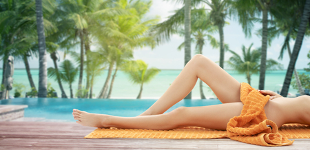 people, summer, beauty and vacation concept - close up of woman legs with orange towel at resort beach with palms and pool photo