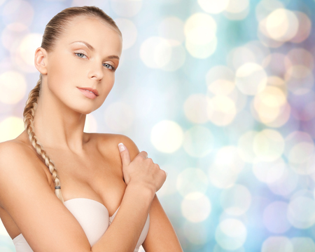 light blue lingerie: beauty, people and body care concept - beautiful young woman with bare shoulders over blue holidays lights background Stock Photo
