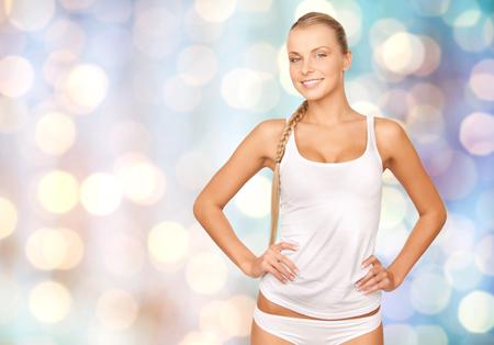 ropa interior: gente, belleza, cuidado del cuerpo y el concepto de moda - mujer joven hermosa feliz en la ropa interior de algodón durante las vacaciones azules fondo de las luces