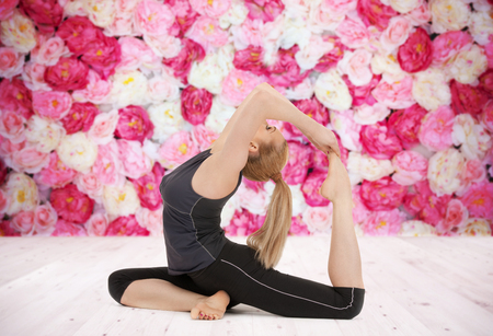 counterbalance: sport, fitness, yoga, people and health concept - happy young woman doing headstand exercise on wooden floor over wall of flowers background Stock Photo