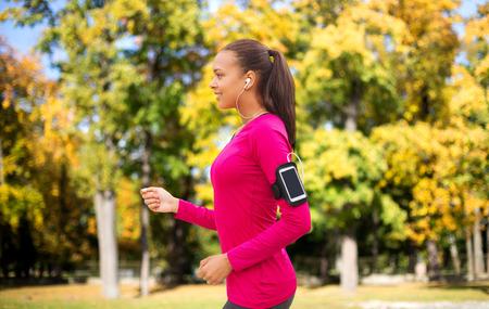 deportistas: deporte, fitness, la tecnología y las personas concepto - sonriente joven mujer afroamericana corriendo con el teléfono inteligente y los auriculares sobre el fondo del parque del otoño