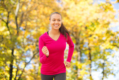 american sport: fitness, sport, training and people concept - smiling african american woman running outdoors over autumn trees background