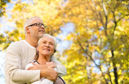 happy seniors: family, age, season and people concept - happy senior couple hugging over autumn trees background Stock Photo
