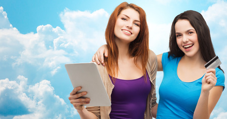 emoney: online shopping, e-money, commerce, people and technology concept - two smiling teenage girls or young women with tablet pc computer and credit card over blue sky with clouds background