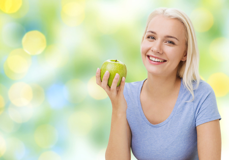 summer diet: healthy eating, organic food, fruits, diet and people concept - happy woman eating green apple over summer green holidays lights background Stock Photo