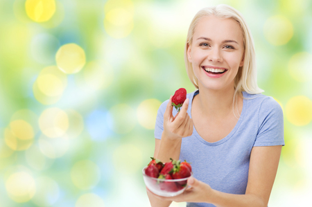 summer diet: healthy eating, food, fruits, diet and people concept - happy woman eating strawberry over summer green holidays lights background