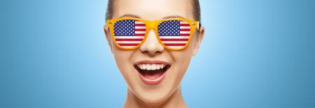 人、愛国心、民族の誇りと独立記念日コンセプト - アメリカの国旗とサングラスで幸せな 10 代の少女