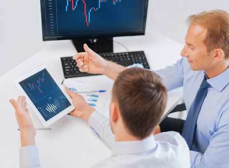 business money: business, money and office concept - businessmen with notebook and tablet pc discussing forex chart on meeting