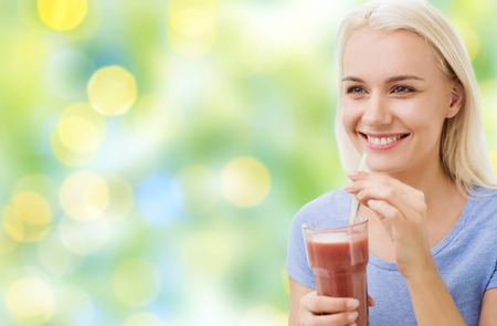 loss weight: healthy eating, vegetarian food, dieting and people concept - smiling woman drinking juice or shake from glass over summer green holidays lights background Stock Photo