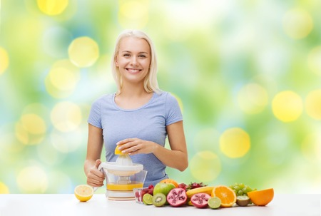 juice squeezer: healthy eating, vegetarian food, diet, detox and people concept - smiling woman with squeezer squeezing fruit juice over summer green holidays lights background