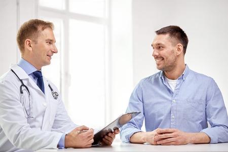 medicina, cuidados de saúde, as pessoas e o conceito do cancro da próstata - médico do sexo masculino feliz com prancheta e reunião paciente e falando no hospital