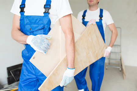 basura: building, carpentry, repair, teamwork and people concept - close up of builders carrying wooden boards