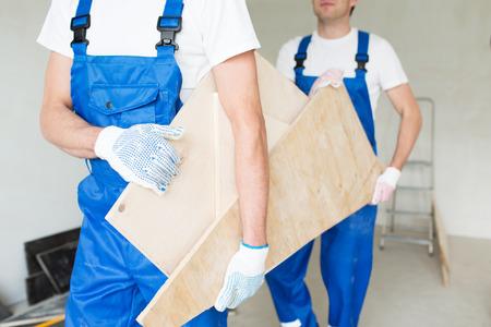 basura: Construcción, carpintería, reparación, trabajo en equipo y concepto de la gente - cerca de constructores que llevan tablas de madera
