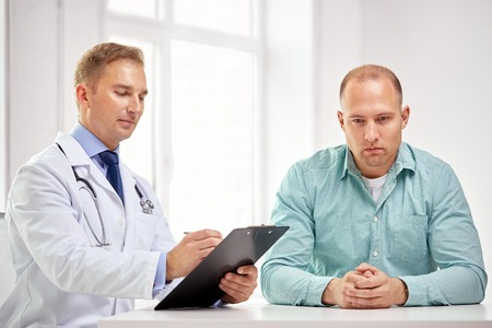 medicine, health care, people and prostate cancer concept - male doctor with clipboard and patient meeting and talking at hospital