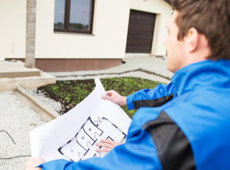 boilersuit: building, construction and people concept - close up of builder with blueprint front of house outdoors