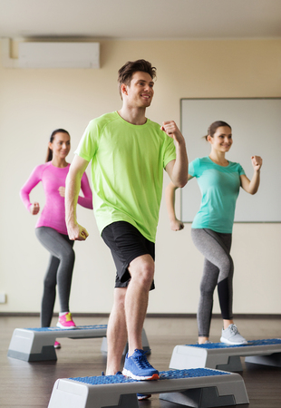 aerobics: fitness, sport, training, aerobics and people concept - group of people working out with steppers in gym