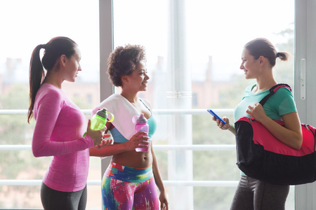 water sport: fitness, sport, training and lifestyle concept - group of happy women with bottles of water, smartphone and bag talking in gym