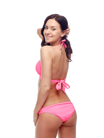 sexy pose: people, fashion, swimwear, summer beach and sexual concept - happy young woman in pink bikini swimsuit looking back Stock Photo