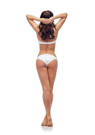 people, fashion, swimwear, summer beach and beauty concept - young woman in white bikini swimsuit from back Stock Photo