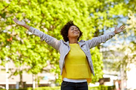 manos abiertas: la gente, la raza, el origen étnico y el concepto de retrato - feliz mujer joven del afroamericano con los brazos abiertos en el parque de verano