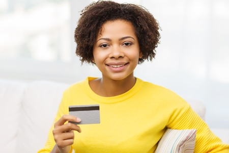 emoney: people, bank, shopping and e-money concept - happy african american young woman sitting on sofa with credit or debit card at home