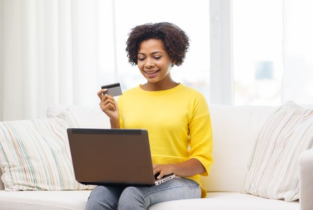 emoney: people, internet bank, online shopping, technology and e-money concept - happy african american young woman sitting on sofa with laptop computer and credit card at home