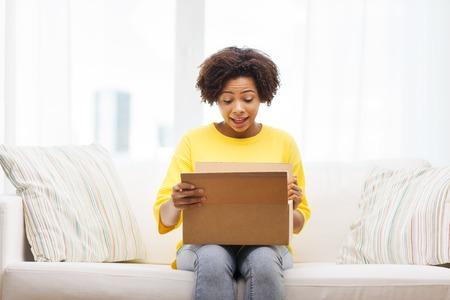 la gente, la entrega, el transporte y el concepto de servicio postal - feliz cuadro afroamericano apertura mujer joven de cartón o paquete en casa Foto de archivo