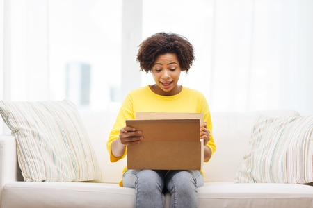 people, delivery, shipping and postal service concept - happy african american young woman opening cardboard box or parcel at home Stockfoto