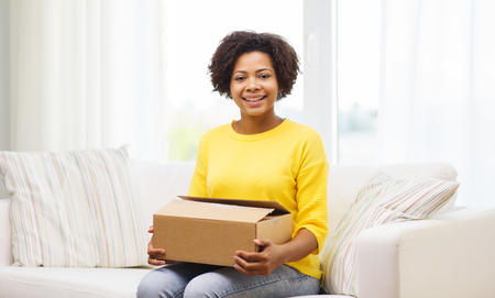 parcel: people, delivery, shipping and postal service concept - happy african american young woman holding open cardboard box or parcel at home