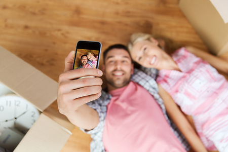 view girl: new home, technology, people, repair and moving concept - happy couple taking selfie with smartphone and lying on floor among cardboard boxes at home