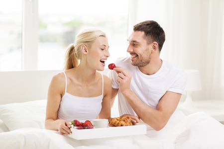 people, love, care and happiness concept - happy couple having breakfast in bed and eating strawberries at home