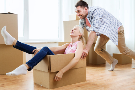 moving box: home, people, moving and real estate concept - happy couple having fun and riding in cardboard boxes at new home
