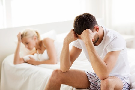 relationship difficulties: people, relationship difficulties, conflict and family concept - unhappy couple having problems at bedroom Stock Photo