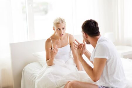 unhappy people: people, relationship difficulties, conflict and family concept - unhappy couple having argument at bedroom Stock Photo