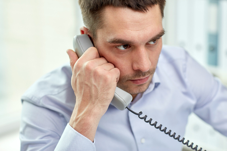 business, people and communication concept - face of angry businessman calling on phone in office