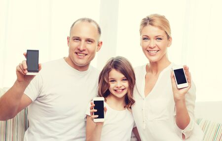 mobile phone screen: family, child, technology and home concept - smiling parents and little girl with blank black screen smartphones at home