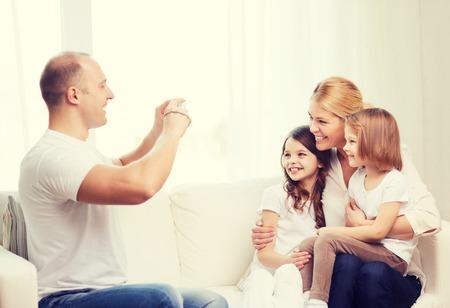 niños sonriendo: familia, los niños, la fotografía y el concepto de hogar - sonriendo padre feliz teniendo imagen de la madre y dos hijas en el hogar