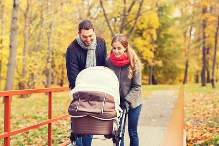 pram: love, parenthood, family, season and people concept - smiling couple with baby pram in autumn park