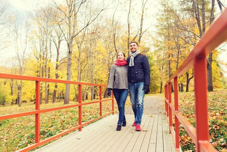 love park: love, relationship, family, season and people concept - smiling couple hugging on bridge in autumn park