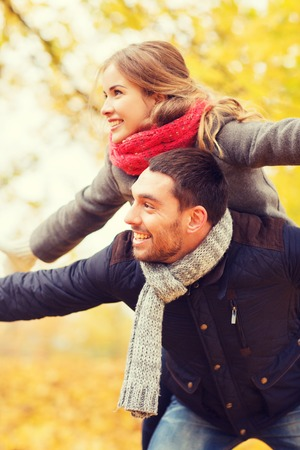 love, relationship, family and people concept - smiling couple having fun in autumn park Stock Photo