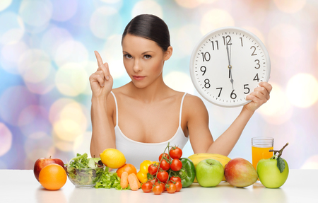 warning lights: people, eating and diet concept - woman with healthy food holding big clock, pointing finger up and warning over blue lights background