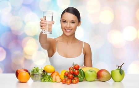 personas saludables: Personas, la dieta vegetariana y el concepto - mujer asiática feliz con el alimento sano que muestra vaso de agua sobre fondo azul luces