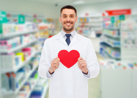 charitable: medicine, pharmacy, people, health care and pharmacology concept - happy male pharmacist holding red heart shape over drugstore background