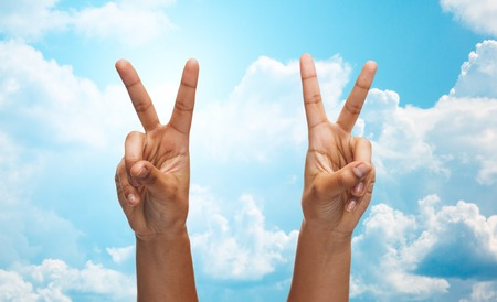 v shape: gesture, people and body parts concept - african woman two hands showing victory or peace over blue sky and clouds background