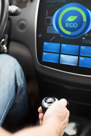 mode transport: transport, modern, green energy, technology and people concept - male hand on gearshift and car eco system mode on screen Stock Photo