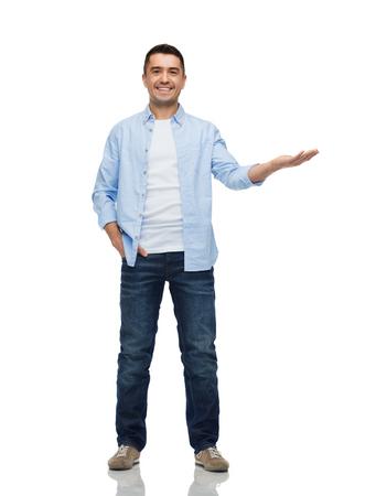 geluk, gebaar en mensen concept - lachende man met iets denkbeeldige op lege palm Stockfoto