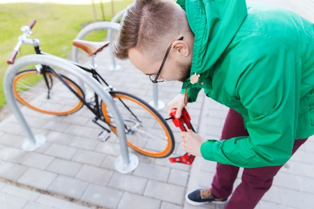 blocking: people, security, safety and lifestyle - young hipster man fastening fixed gear bike with blocking lock on city street parking