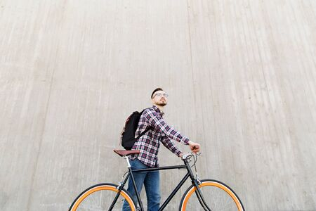 travel gear: people, travel, tourism, leisure and lifestyle - happy young hipster man with fixed gear bike and backpack on city street